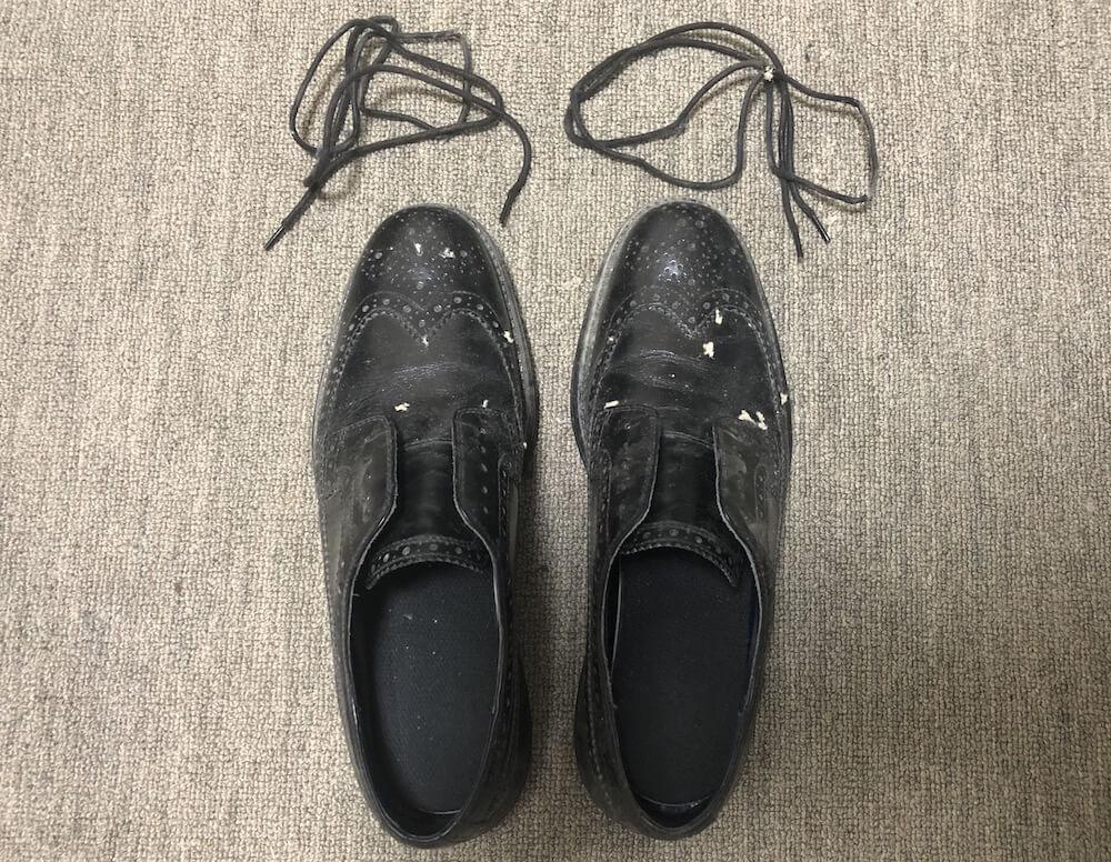 革靴の靴紐を外す
