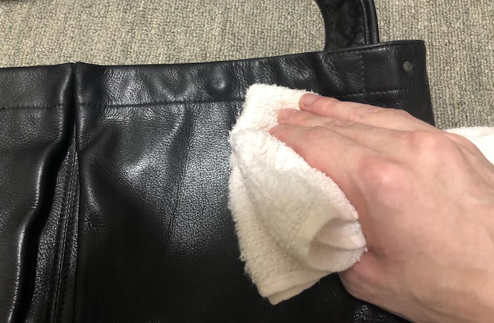 消毒用エタノールを含んだタオルで革バッグを拭く